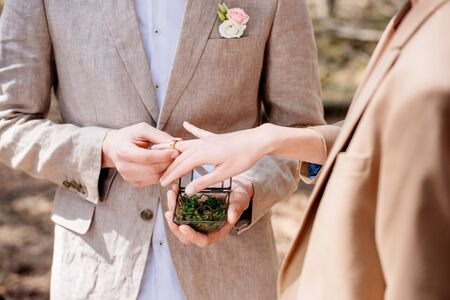 cropped view of bridegroom and bride putting wedding ring on finger Stock Photo