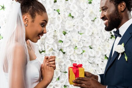 surprised african american bride looking at present near happy bridegroom and flowers Stock Photo