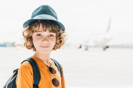 schattig preteen kind in hoed kijkend naar camera op luchthaven met kopieerruimte