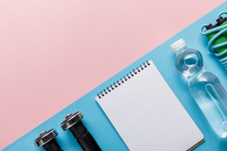 flat lay with dumbbells, empty notebook, bottle of water and skipping rope on pink and blue background Reklamní fotografie