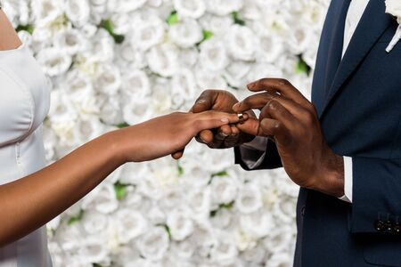 cropped view of african american man putting wedding ring on finger of bride near flowers
