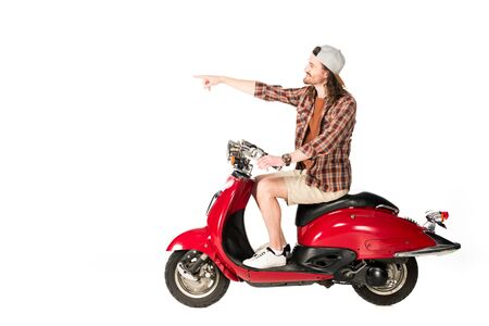 side view of young man sitting on red scooter and pointing with finger isolated on white Imagens - 128145760
