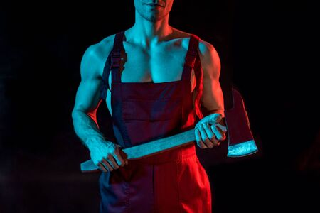 cropped view of shirtless fireman holding flat head axe on black