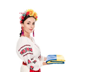 side view of brunette young woman in national Ukrainian costume holding flag isolated on white