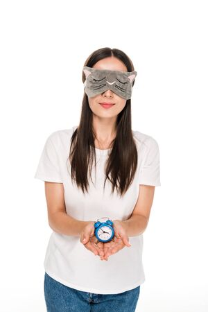 brunette young woman in cat sleeping eye mask holding toy alarm clock isolated on white
