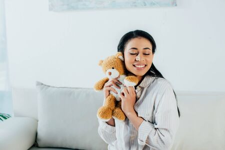 happy latin woman with closed eyes hugging teddy bear while sitting on couch at home Stock Photo