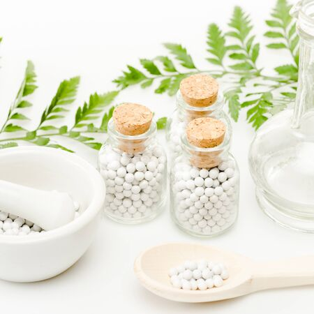 glass bottles with small round pills near mortar and pestle, wooden spoon, jar and green leaves on white
