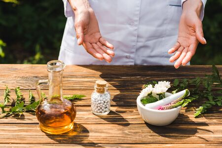 cropped view of woman near wooden table with plants and bottle with pills Stock fotó