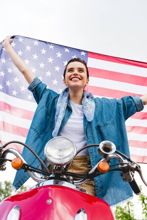 low angle view of beautiful girl standing on red scooter, holding American flag and smiling on sky background