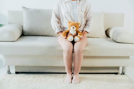 cropped shot if young woman sitting on couch at home and holding teddy bear