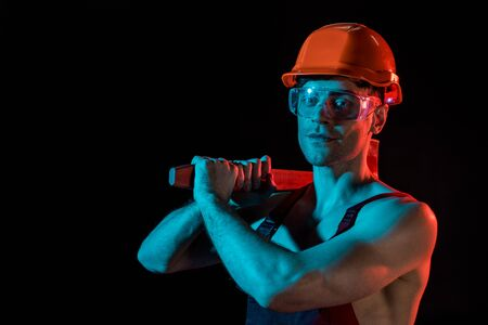 sexy fireman in overall, hardhat and protective goggles holding flat head axe isolated on black
