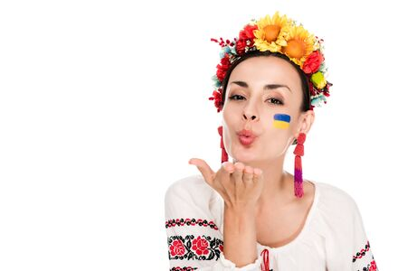brunette young woman in national Ukrainian embroidered shirt and floral wreath blowing kiss isolated on white