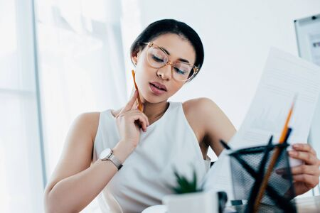 selective focus of focused latin businesswoman doing paperwork in office