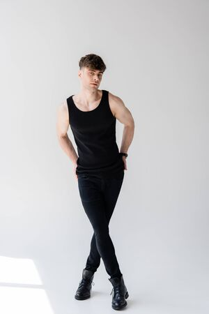 full length view of man in sleeveless shirt standing on grey Banco de Imagens