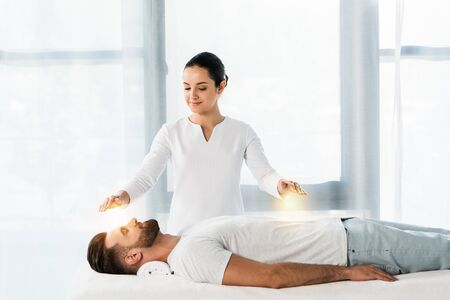 attractive woman putting hands above body while healing handsome bearded man