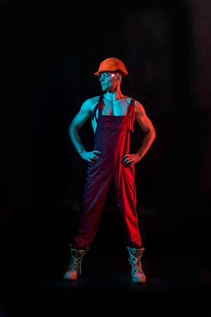 full length view of sexy fireman in overall, hardhat and protective goggles with arms akimbo on black