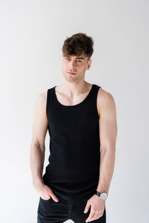 man in black sleeveless shirt with hand in pocket isolated on grey Banco de Imagens