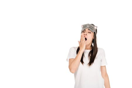 brunette young woman in cat sleeping eye mask yawing isolated on white