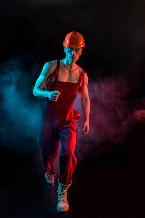 full length view of shirtless fireman in overall, hardhat and protective goggles in smoke on black