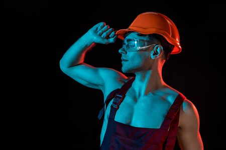 sexy fireman in overall, hardhat and protective goggles isolated on black Reklamní fotografie