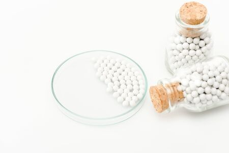 selective focus of round small pills in glass petri dish near bottles with wooden corks isolated on white Foto de archivo - 128146388