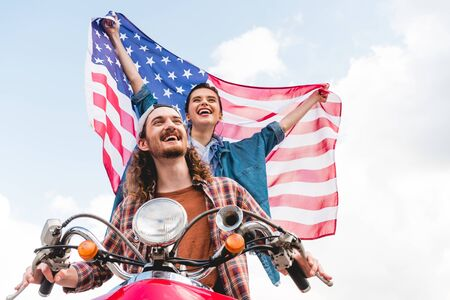 low angle view of beautiful girl riding with young man on red scooter and holding American flag Stok Fotoğraf