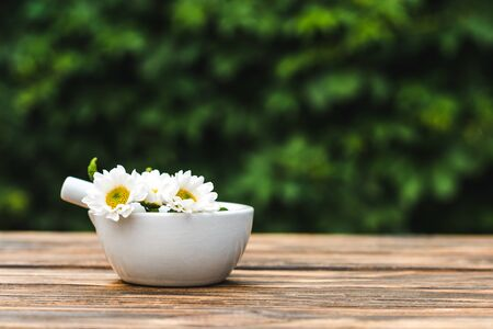 pestle in mortar with chrysanthemum flowers on wooden table Imagens