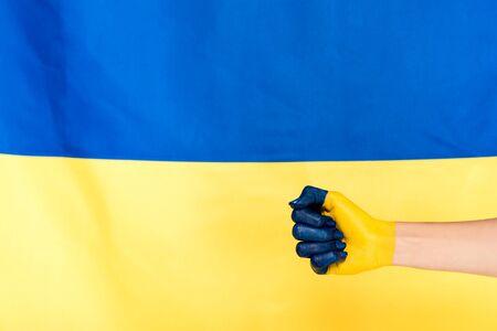 partial view of painted hand on Ukrainian flag background Foto de archivo - 128146488