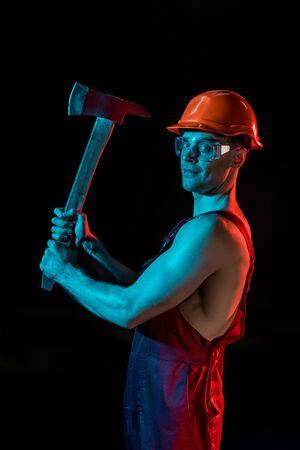 shirtless fireman in overall, hardhat and protective goggles holding flat head axes isolated on black