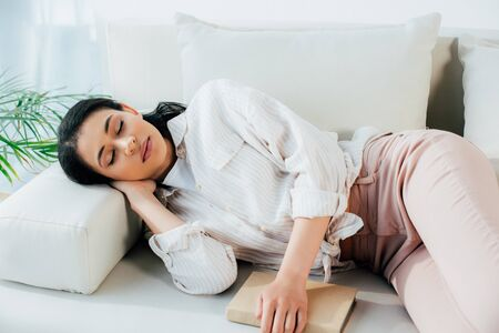 beautiful young woman sleeping with book while lying on couch at home