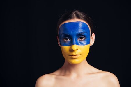 naked young woman with painted Ukrainian flag on skin looking at camera isolated on black