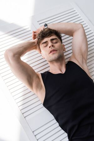 man in black sleeveless shirt lying with closed eyes on grey