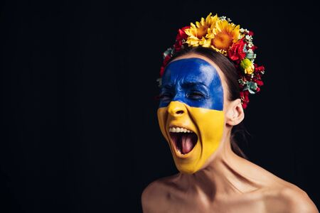 young woman in floral wreath with painted Ukrainian flag on skin screaming isolated on black