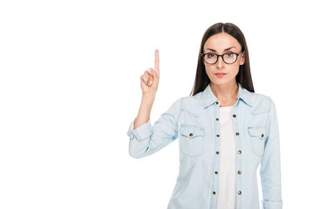 brunette girl in glasses in denim jacket pointing with finger upwards isolated on white