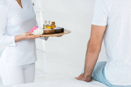 cropped view of masseur holding tray with bottles of oil, bowls with sea salt and flowers near man in spa center Imagens