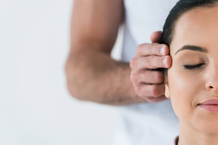 cropped view of masseur putting hands on temples of woman isolated on white