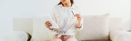 przycięte zdjęcie Latynoski trzymającej kartę kredytową i używającej cyfrowego tabletu siedząc na kanapie Zdjęcie Seryjne