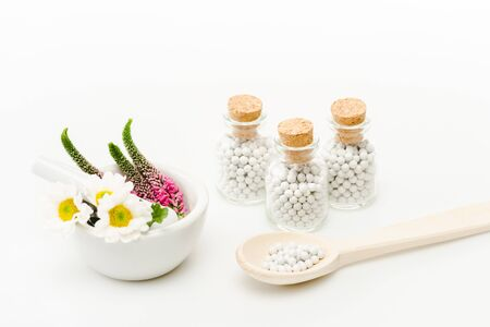 flowers in mortar near pestle and glass bottles with pills on white