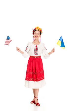 happy brunette young woman in national Ukrainian costume holding American and Ukrainian flags isolated on white
