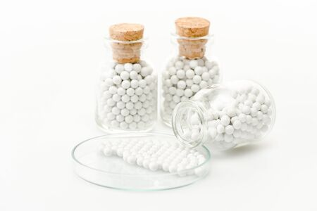 selective focus of round pills in glass petri dish near bottles with wooden corks isolated on white