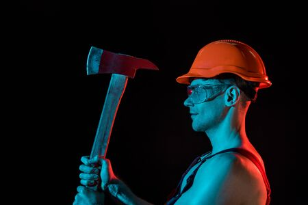 side view of sexy fireman in hardhat and protective goggles holding flat head axe isolated on black Stock Photo