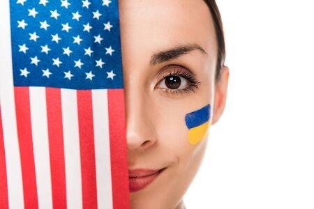lächelnde junge Frau mit gemalter ukrainischer Flagge auf Gesicht, die amerikanische Flagge lokalisiert auf Weiß hält