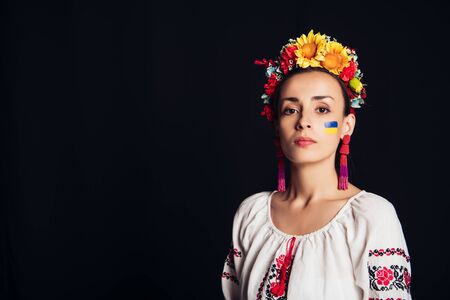 brunette young woman in national Ukrainian costume and floral wreath looking at camera isolated on black