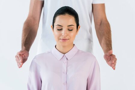 cropped view of healer putting hands near attractive woman with closed eyes isolated on white