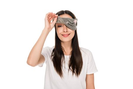 smiling brunette young woman in cat sleeping eye mask isolated on white