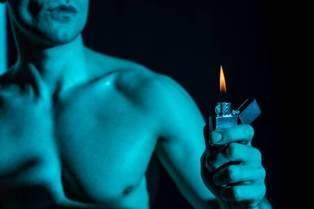 cropped view of sexy shirtless man holding lighter in darkness Stock fotó