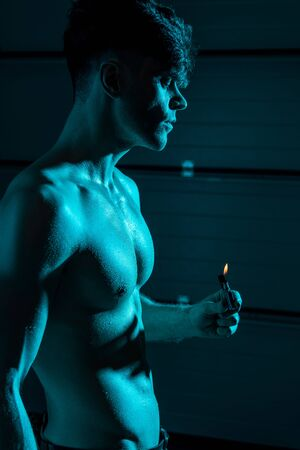 sexy shirtless muscular man holding lighter in darkness Stok Fotoğraf - 128146423