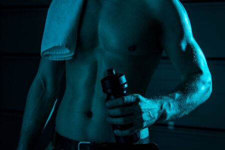 partial view of sexy shirtless man with towel holding sport bottle in darkness