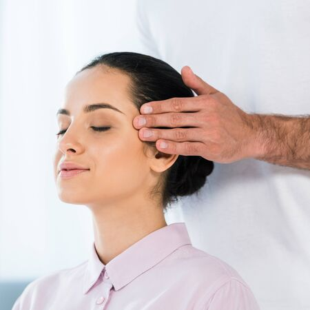 cropped view of man putting hands on temples of attractive woman with closed eyes Imagens