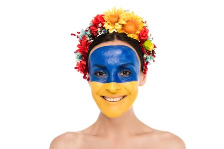 young woman in floral wreath with painted Ukrainian flag on skin smiling isolated on white Stock fotó
